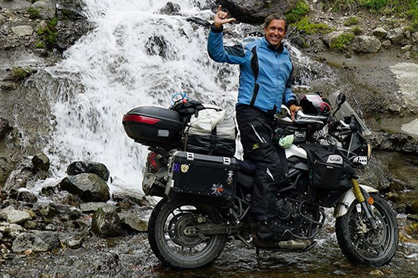 Nomad Roy on his motorcycle in a river