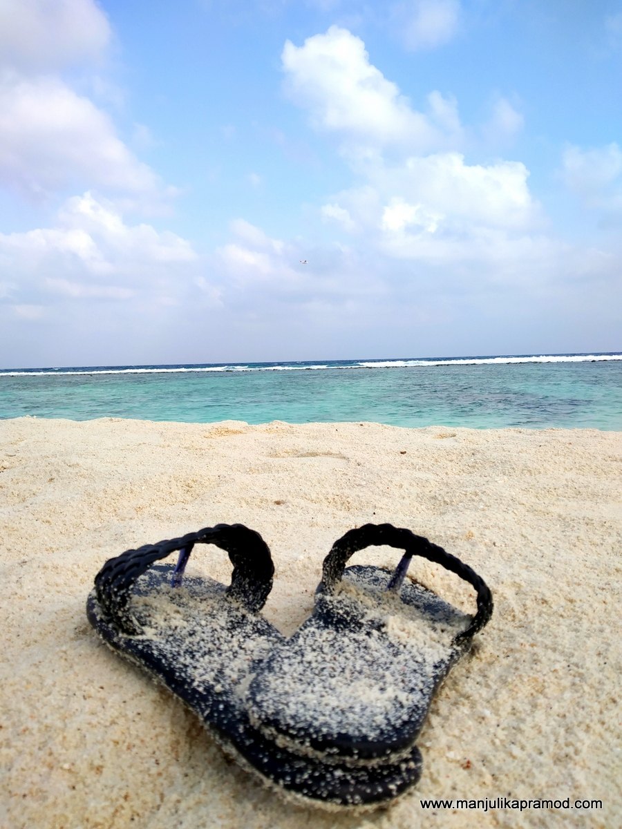 Slippers on white powdery sand