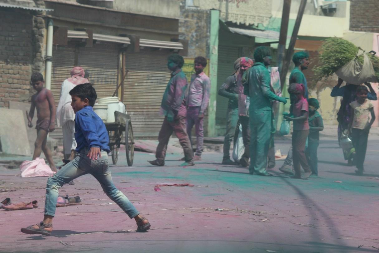 A boy playing Holi on the streets of Govardhan