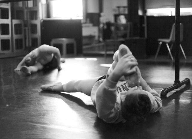 Dancers stretch before dance class begins.
