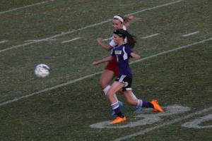Emma Overstreet (12, #12) blocks a shot from a Male attacker. Photo by Shea Dobson