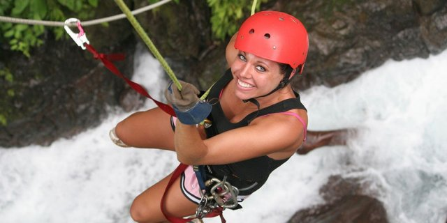 Woman rappelling down waterfall