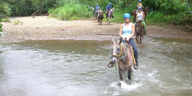 Horback riding through jungle creek