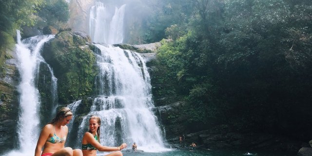 Two people sitting in front of a large waterfall