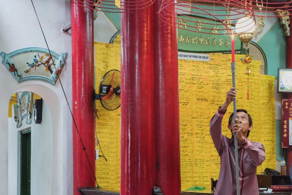 man lighting insense at a temple in Can tho, Vietnam