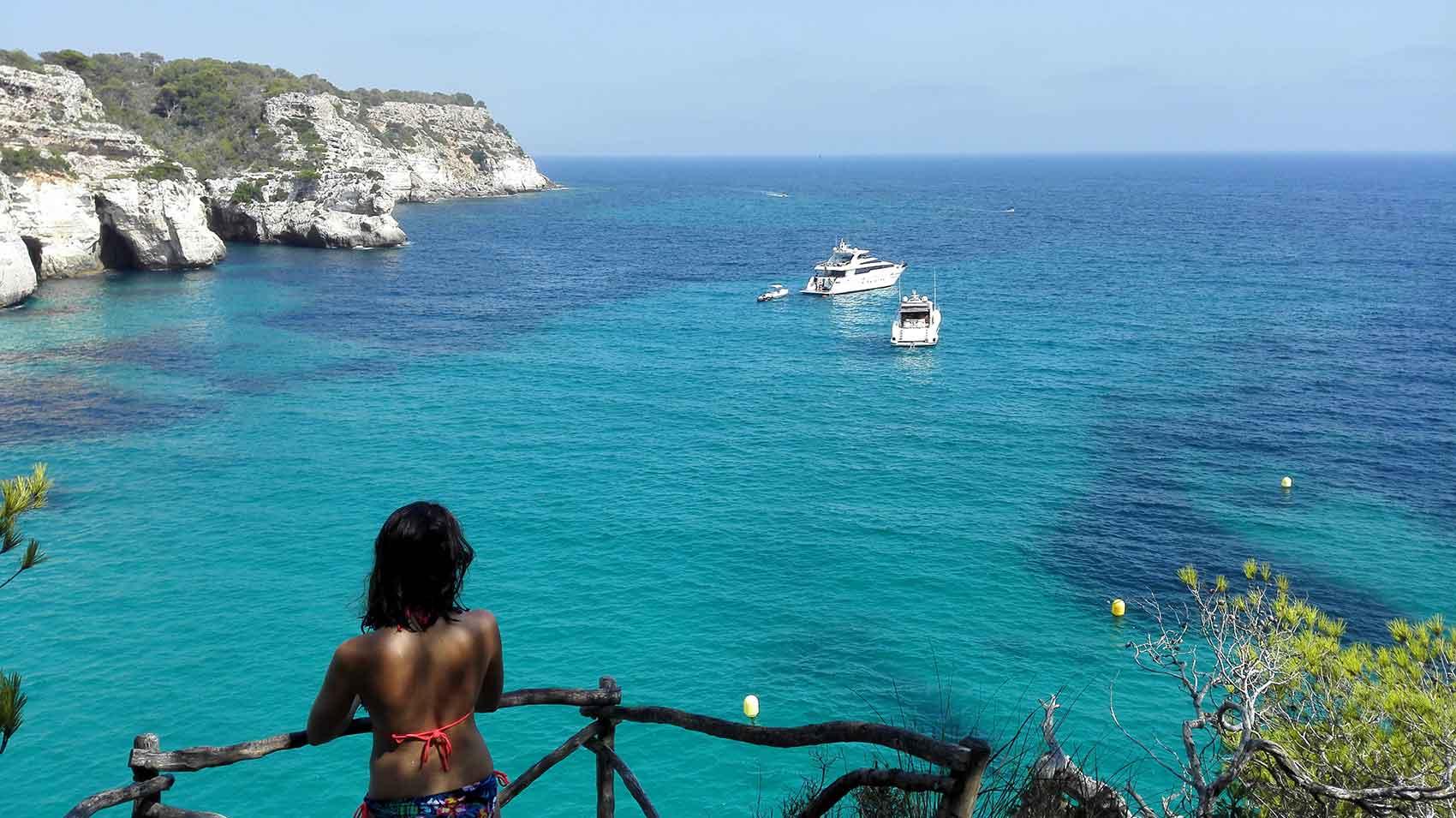 Anaïs perchée sur les falaises de la Cala Macarella, avec une belle vue sur la mer Méditerranée.