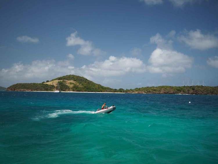 Damien part en annexe faire du kitesurf entre les îles des Tobago Cays.