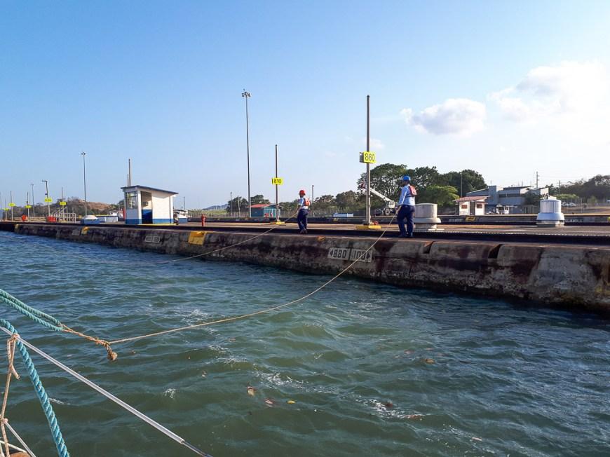 Les agents du canal qui suivent avec les pommes de touline le long des écluses panaméennes.