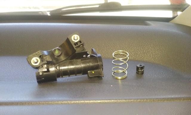 Na foto acima vemos o cilindro já retirado. Ao seu lado uma mola do conjunto e parte do cilindro quebrado e a causa do defeito.