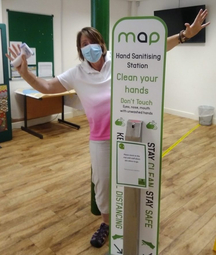 Senior Advice worker Julie wearing a mask and demonstrating the hands-free sanitising station at MAP Great Yarmouth.
