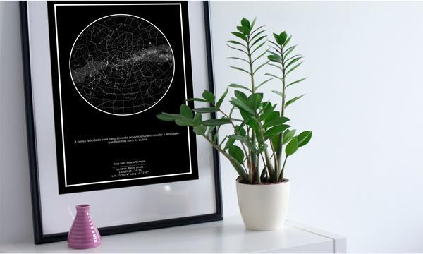 Imagem de quadro do Mapa do Céu preto encostado na parede, ao lado de um vaso com planta e vaso rosa