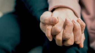 duas pessoas de mão dada, demonstrando amor ao próximo no isolamento social