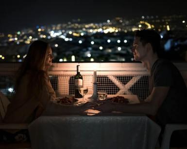 Casal bebe vinho em varanda, num jantar romântico