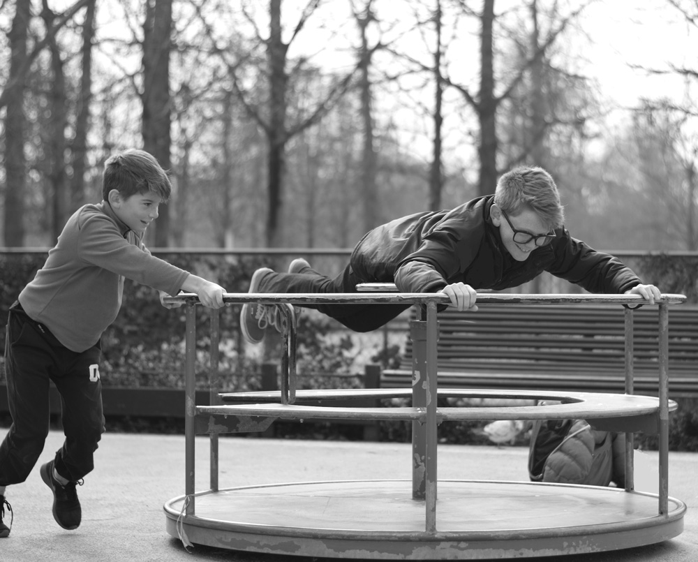 Photo of brothers playing on the merry-go-round at Tuileries playground in Paris.