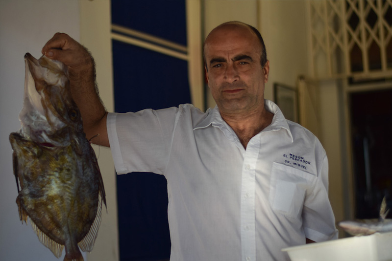 image of a waiter holding a fresh caught fish in a restaurant in Cabo de Gata Natural Park in Spain
