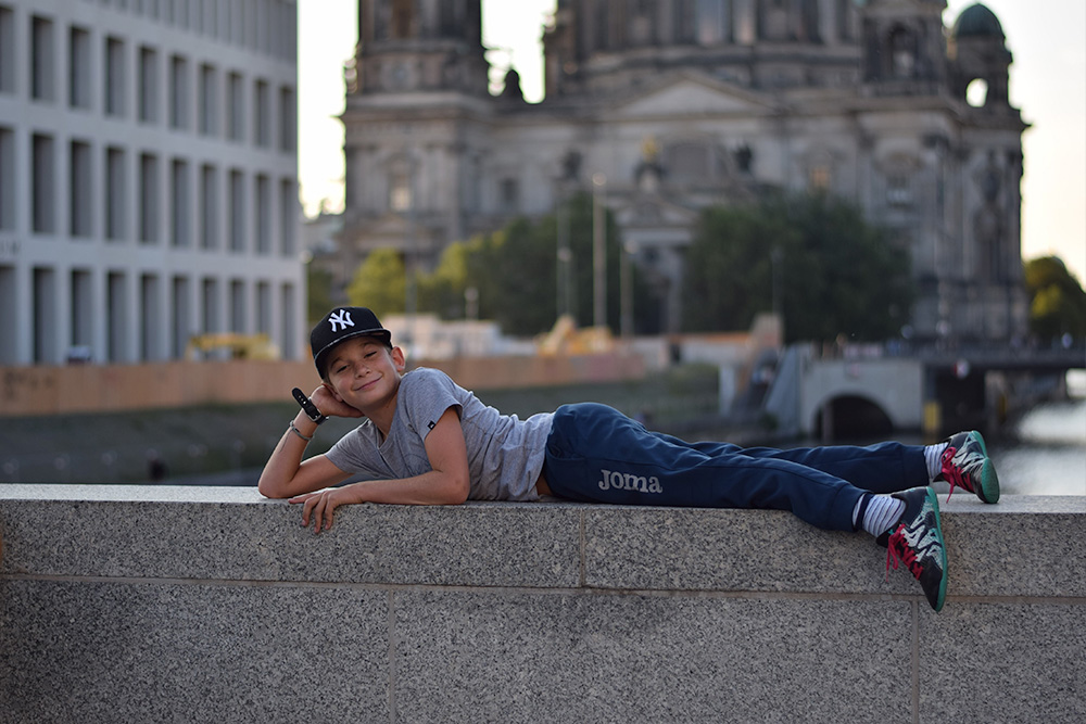 Photo of a boy (a tourist) posing on the River Spree in Berlin, Germany.