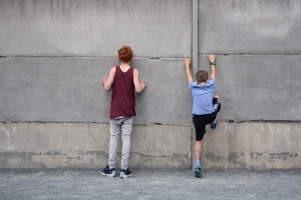 Photo of brothers (tourists) standing at the old Berlin Wall, touching the wall, trying to peer through, one of the boys is trying to climb the wall.