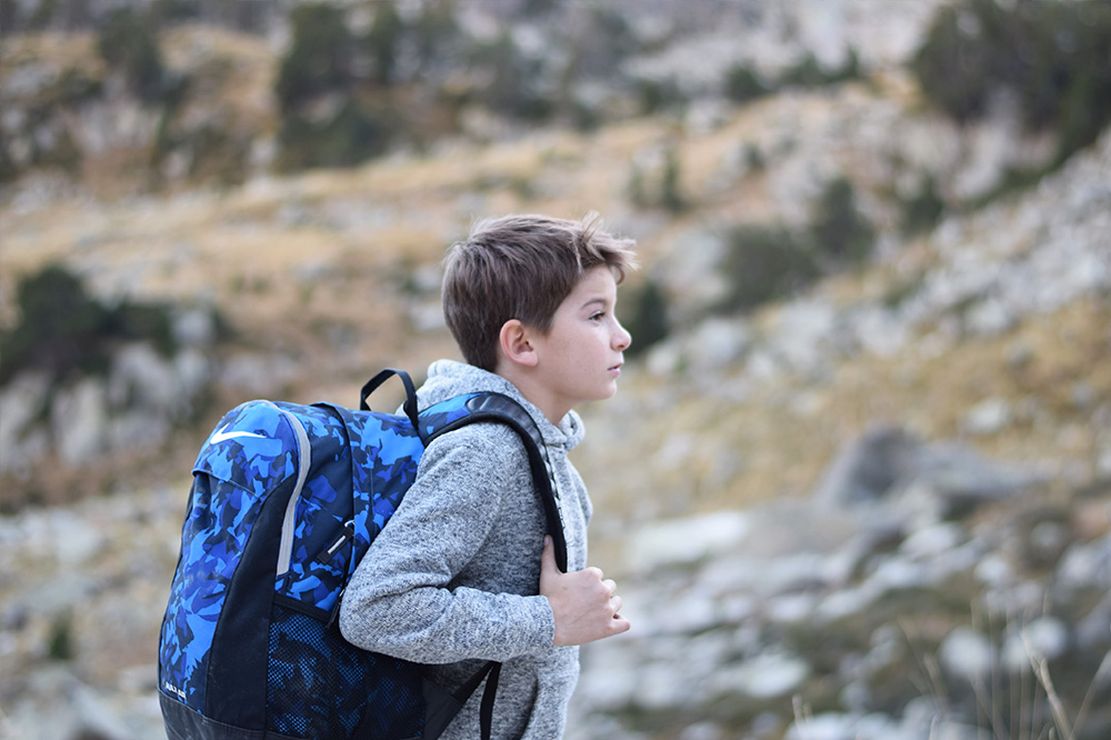 A boy with his backpack on preparing to hike up a hill in the Spanish Pyrenees.
