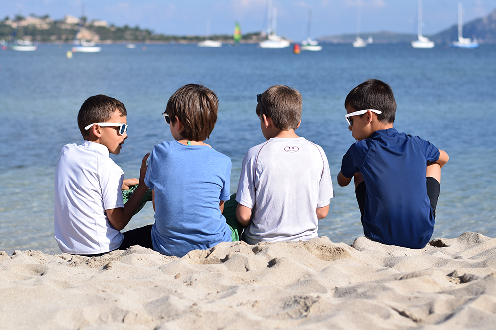 A photo of 4 boys sitting on a white sandy beach together in Mallorca, Spain.