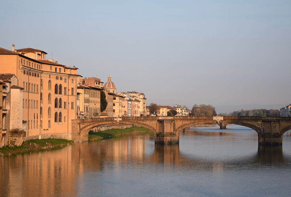 Photo of a river running through Florence, Italy at sunrise