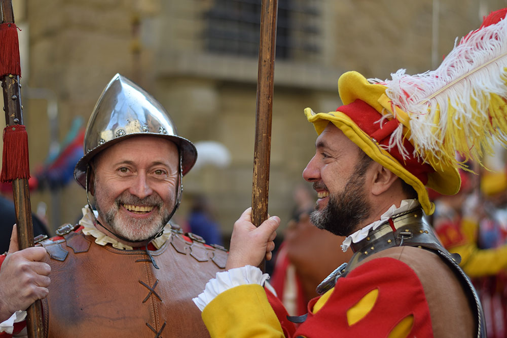 A photo of two men smiling in period costume during an Easter celebration in Florence, Italy
