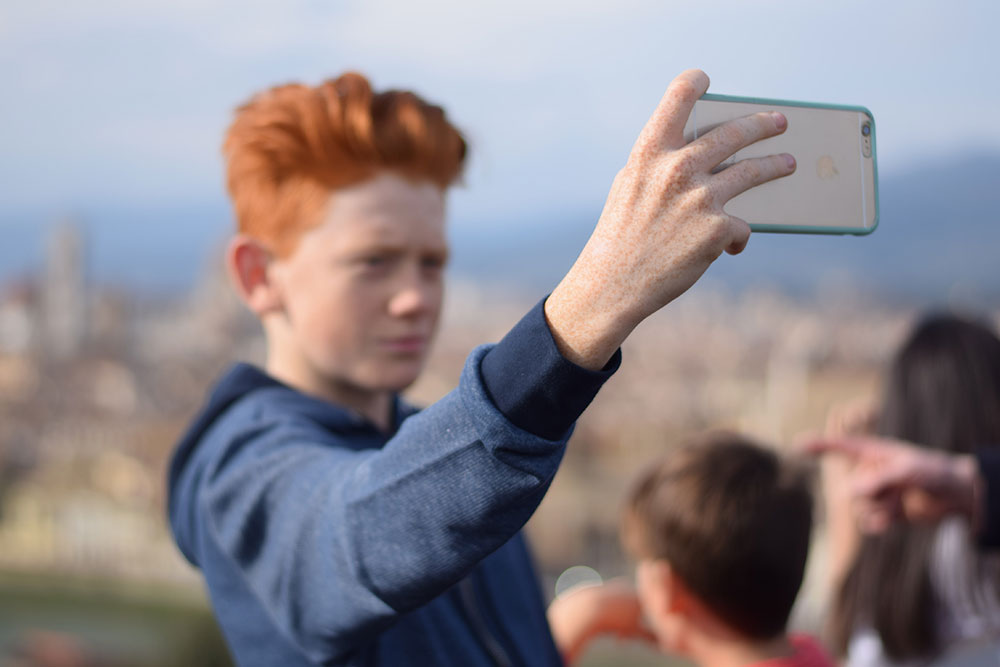 Photo of a boy taking a 'selfie' overlooking the cit of Florence, Italy