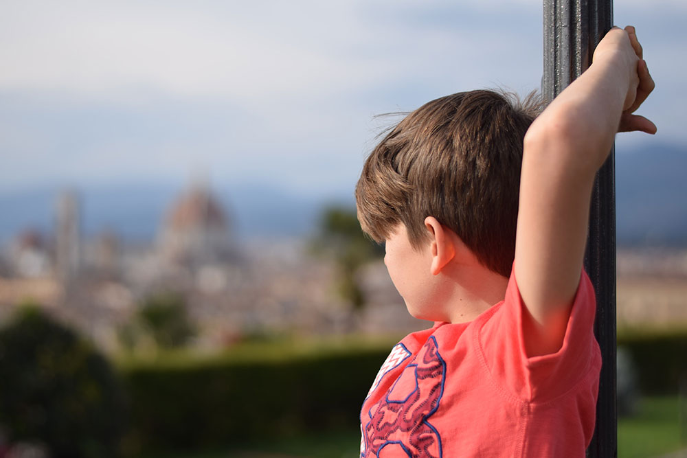 Photo of a boy looking out across the city of Florence, Italy