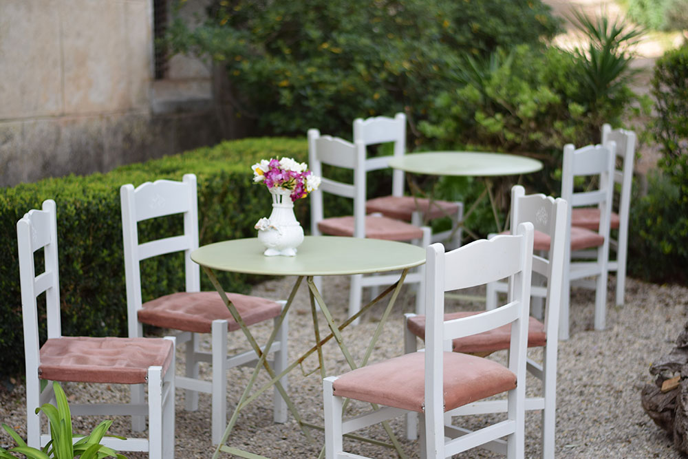 White chars with pink velvet seats nested around small tables in the garden at Finca Son Mico in Mallorca, Spain.