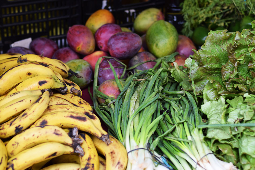 Photograph of bananas, spring onions, mangos and lettuce at the Santa Maria market in Mallorca, Spain.