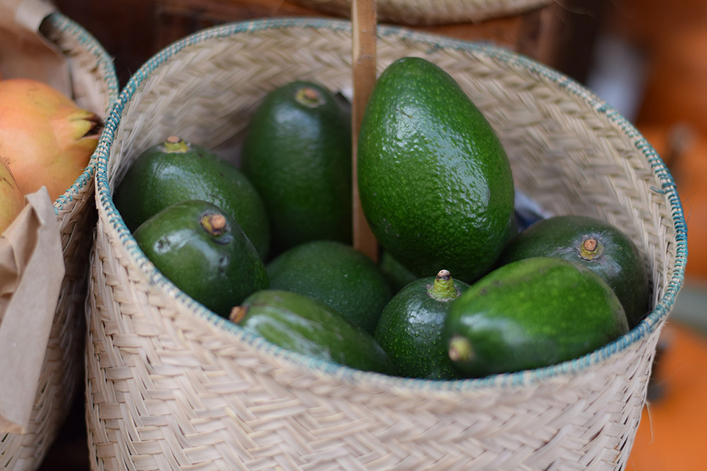 Photograph of a basket of avocados at the Santa Maria market in Mallorca, Spain.