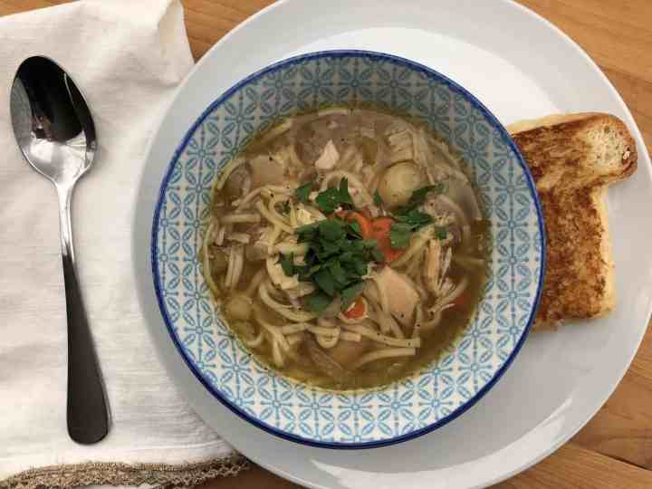 chicken noodle soup in a bowl with grilled cheese sandwich