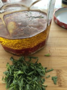 ingredients in a jar for making citrus hazelnut vinaigrette