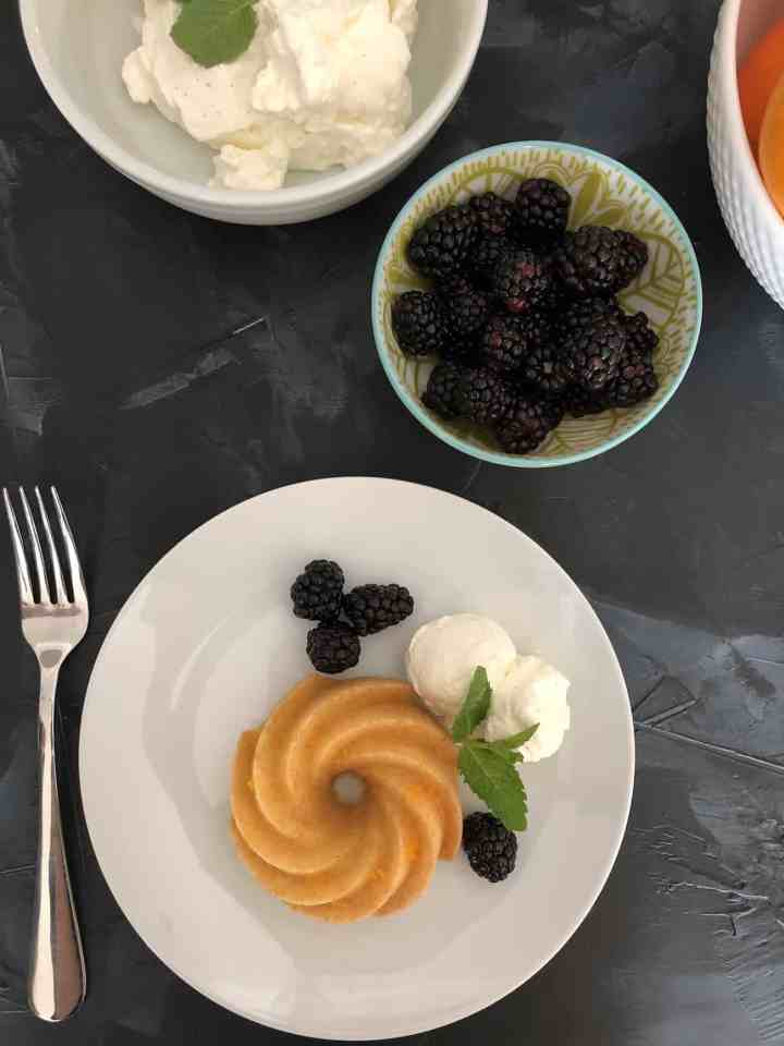 orange bundlette with bowl of whipped cream, blackberries, and bowl of oranges