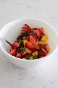 mixing up mango strawberry salsa