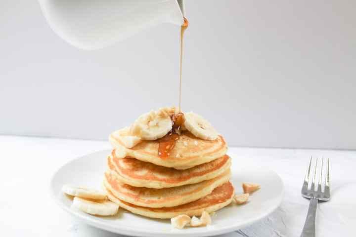 pouring syrup on banana macadamia nut pancakes