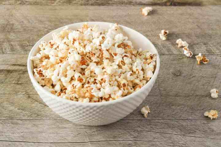 bowl of maple sea salt popcorn on gray wood