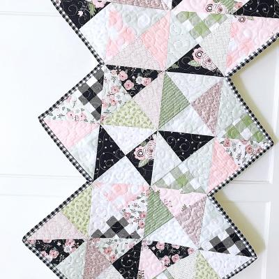 Rhapsody Whirl table runner pattern for 1 charm pack and features a zigzag edge.