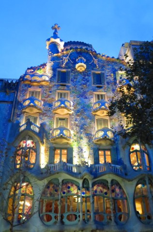 "Casa Batlló: a Gaudi masterpiece covered in ""tiny mosaic tiles and mask-shaped balconies and topped with a shimmering roof of lizard-like scales."""