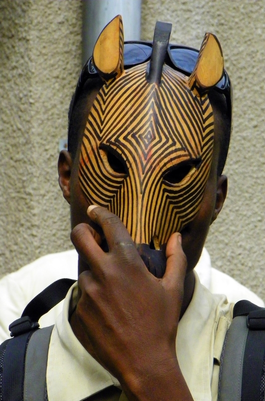 A boy in Africa covers his face with a hand carved mask.