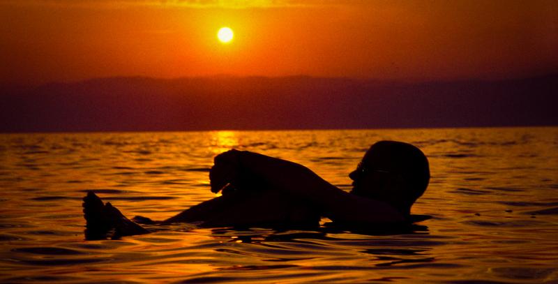 Taking a bath in the Dead Sea by Sunset, Jordan