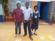 Ramos, Witness and Joyce in the yard of the Wukani education facility