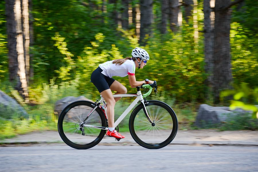 Simple Ways to Improve Bike Aerodynamics Young Woman Cyclist Riding Road Bicycle on Free Road in the Forest at Hot Summer Day. Healthy Lifestyle Concept.