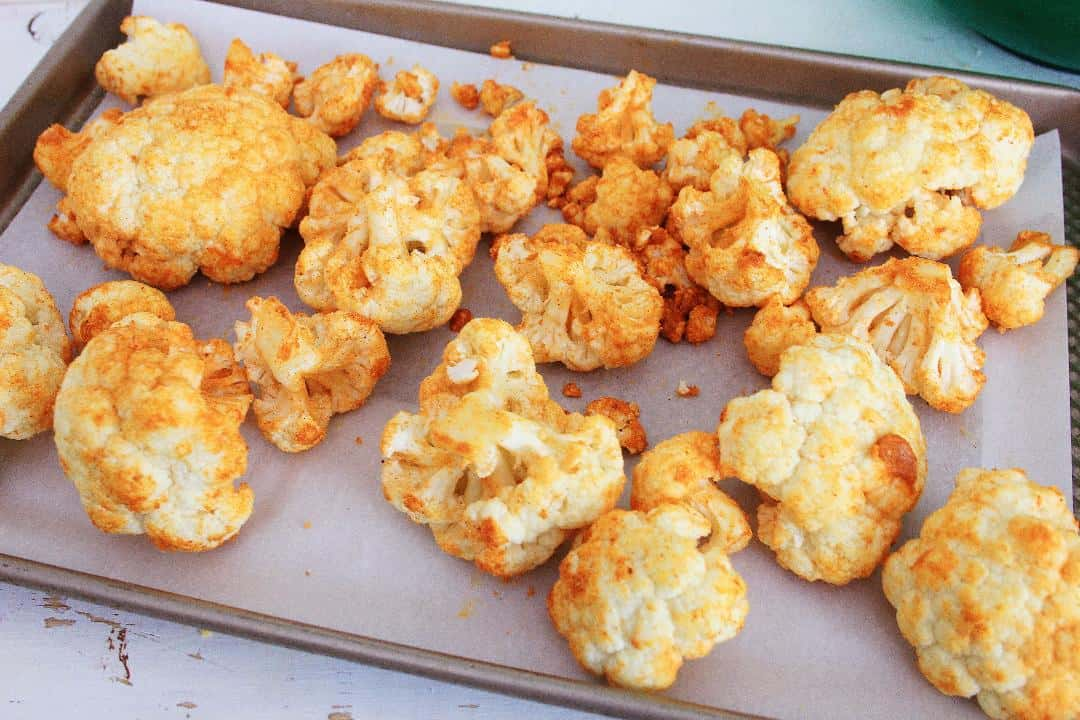 Seasoned cauliflower on sheet pan lined with parchment paper.