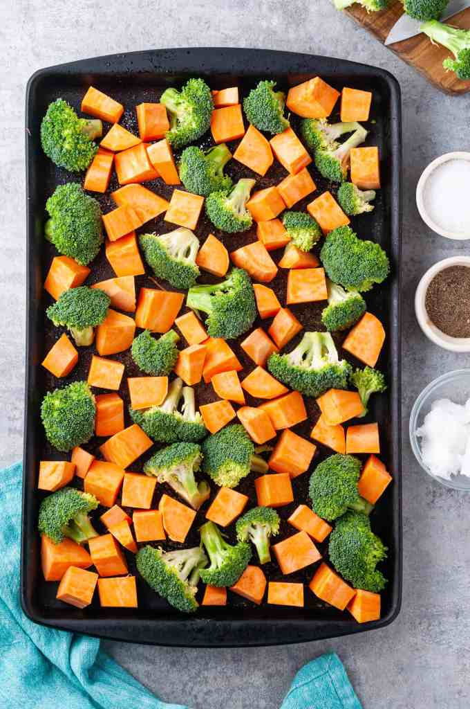 Broccoli and sweet potatoes on a baking sheet with coconut oil, salt and pepper to the right side of the baking sheet.