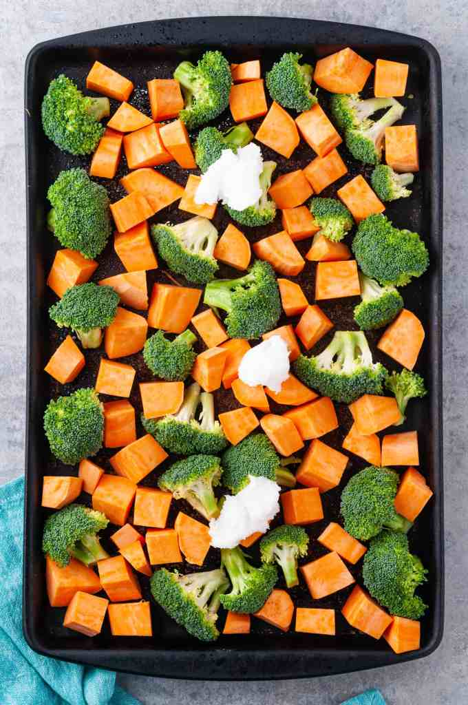 Broccoli and sweet potatoes on baking sheet with solid coconut oil on top.