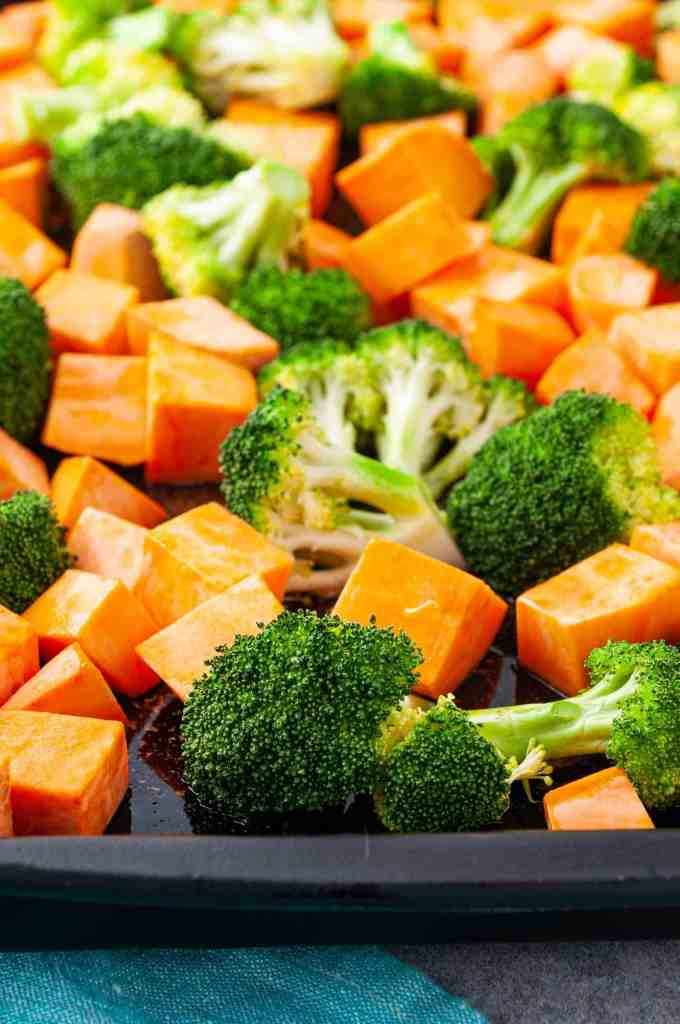 Closeup of broccoli and sweet potatoes on baking pan with melted coconut oil