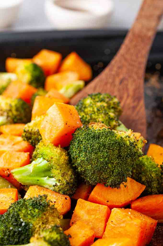 Roasted broccoli and sweet potatoes in coconut oil with a wooden spoon