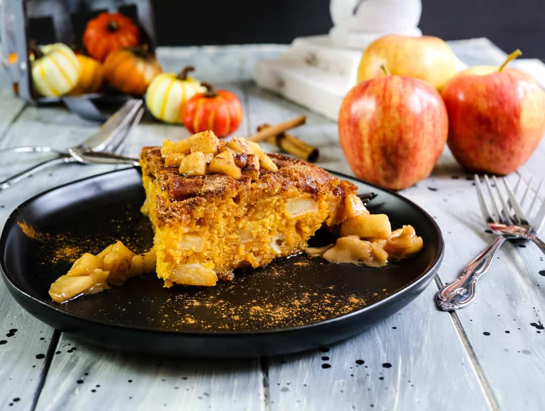 Cinnamon Apple Pumpkin Cake on a white wood background with apples and pumpkins.