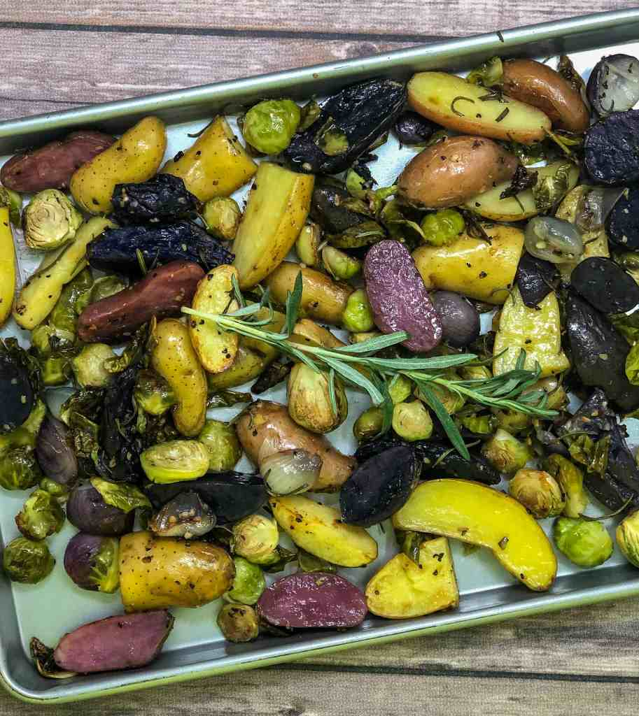 A sheet pan of roasted vegetables including brussels sprouts, fingerling potatoes, and shallots with fresh rosemary