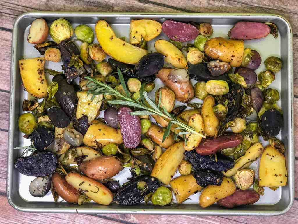 Roasted Fingerling Potatoes and Brussels Sprout with a sprig of fresh rosemary on a sheet pan